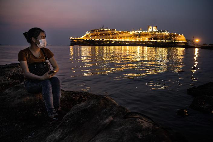 SIHANOUKVILLE - FEBRUARY 17 : A Chinese woman looks at the MS Westerdam cruise ship docked nearby in Sihanoukville, Cambodia on February 17, 2020. There are currently 233 passengers and 747 crew members on board who were tested again before they will be allowed to depart. As the ship was declared free of the Coronavirus (COVID-19 ) over 1,000 passengers took charter flights to Phnom Penh, one elderly American woman was later found to be infected while transiting in Malaysia. The cruise ship departed Hong Kong February 1st with 1,455 passengers and 802 crew on board. (Photo by Paula Bronstein/Getty Images )