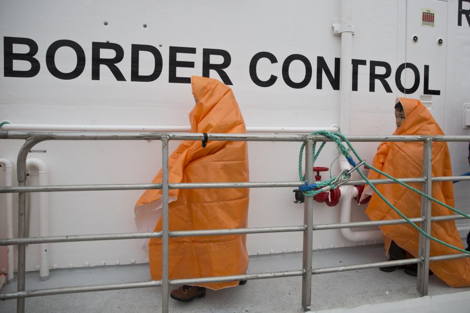 FILE - In this Tuesday, March 22, 2016 file photo, two children prepare to disembark with other 53 migrants and refugees from a Norwegian Frontex patrol vessel after they were rescued near the shores of the Greek island of Lesbos. Human rights lawyers said on Tuesday, May 25, 2021, that they have launched legal action against the European Union's border and coast guard agency at the bloc's top court, accusing Frontex of violating the rights of people trying to seek asylum and other breaches of international law. (AP Photo/Petros Giannakouris, File)