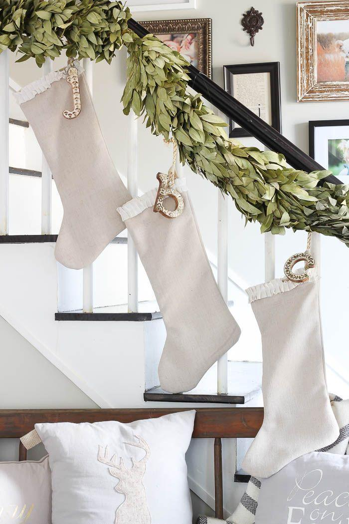 """<p>If you don't have a mantel, hang your stockings with care on the staircase instead. Neutral-colored stocking with a letter-shaped ornament look stunning hanging from a magnolia leaf garland. </p><p><em>Get the tutorial at <a href=""""https://roomsforrentblog.com/2016/11/holiday-housewalk-2016/"""" rel=""""nofollow noopener"""" target=""""_blank"""" data-ylk=""""slk:Rooms for Rent"""" class=""""link rapid-noclick-resp"""">Rooms for Rent</a>.</em></p><p><a class=""""link rapid-noclick-resp"""" href=""""https://www.amazon.com/dp/B07GDSSPKS/ref=twister_B07GDV2P3W?tag=syn-yahoo-20&ascsubtag=%5Bartid%7C10072.g.34479907%5Bsrc%7Cyahoo-us"""" rel=""""nofollow noopener"""" target=""""_blank"""" data-ylk=""""slk:SHOP MAGNOLIA LEAF GARLAND"""">SHOP MAGNOLIA LEAF GARLAND</a></p>"""