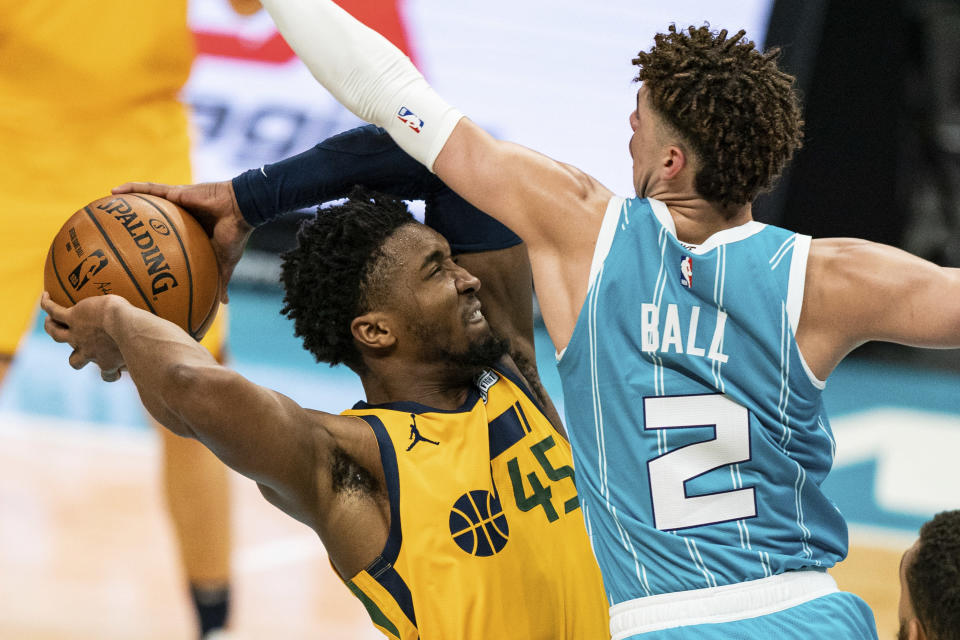Utah Jazz guard Donovan Mitchell (45) drives to the basket while guarded by Charlotte Hornets guard LaMelo Ball (2) during the second half of an NBA basketball game in Charlotte, N.C., Friday, Feb. 5, 2021. (AP Photo/Jacob Kupferman)