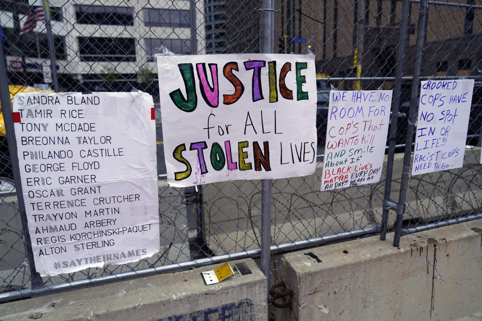 New signs are on a fence at the Hennepin County Government Center, Monday, April 19, 2021, in Minneapolis where closing arguments are being heard in the trial of former Minneapolis police officer Derek Chauvin continues. Chauvin is charged with murder in the death of George Floyd during an arrest last may in Minneapolis. (AP Photo/Jim Mone)