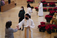 Worshipers receive communion during a Christmas Eve Mass inside the Cathedral of Our Lady of the Angels Thursday, Dec 24, 2020, in Los Angeles. California became the first state to record 2 million confirmed coronavirus cases, reaching the milestone on Christmas Eve as nearly the entire state was under a strict stay-at-home order and hospitals were flooded with the largest crush of cases since the pandemic began. (AP Photo/Ashley Landis)