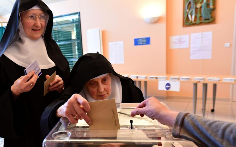 A Benedictine sister of the Sainte-Cecile Abbey casts her ballot at a polling station in Solesmes, northwestern France - Credit: JEAN-FRANCOIS MONIER/AFP