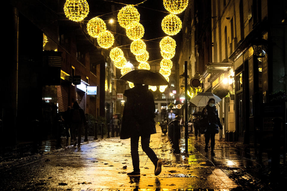 A man crosses a quiet street filled with Christmas lights in central London, Monday November 9, 2020. Wet weather has drenched the London streets during the first full week of a four-week coronavirus lockdown in England, as some are calling to allow businesses to open their doors to kickstart the city economy. (Victoria Jones/PA via AP)