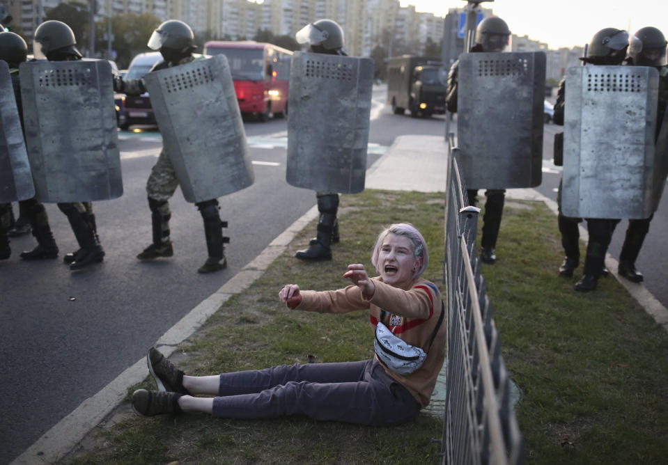 FILE - In this Wednesday, Sept. 23, 2020 file photo, a woman reacts in front of police line during a rally in Minsk, Belarus. Belarus President Alexander Lukashenko has relied on massive arrests and intimidation tactics to hold on to power despite nearly three months of protests sparked by his re-election to a sixth term, but continuing protests have cast an unprecedented challenge to his 26-year rule. (AP Photo/TUT.by, File)