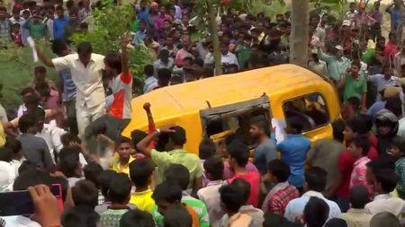 People gather around a school bus after it collided with a train in Uttar Pradesh, India April 26, 2018, in this screen grab taken from video. ANI via REUTERS