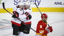 Ottawa Senators' Colin White, left, celebrates his goal with teammate Nicholas Paul as Calgary Flames' Mark Giordano skates away during the second period of an NHL hockey game, in Calgary, Alberta, Sunday, March 7, 2021. (Jeff McIntosh/The Canadian Press via AP)