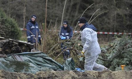 Police experts inspect the crime scene in Gimmlitztal near the town of Hartmannsdorf-Reichenau, south of Dresden, November 29, 2013. A German policeman has been arrested after the chopped-up body of a man he met on a fetishist website for cannibalism was found buried in his garden, police in the eastern city of Dresden said on Friday. REUTERS/Pawel Sosnowski