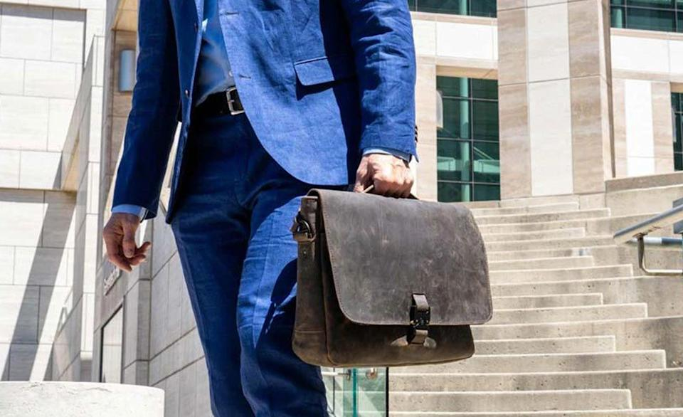 A man in a blue suit holds a brown Waterfield Designs Executive Leather Messenger bag.