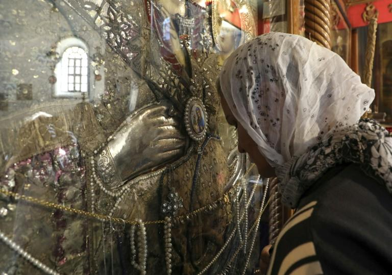 A pilgrim prays in front of an icon of the Virgin Mary at the Church of the Nativity (AFP Photo/HAZEM BADER)