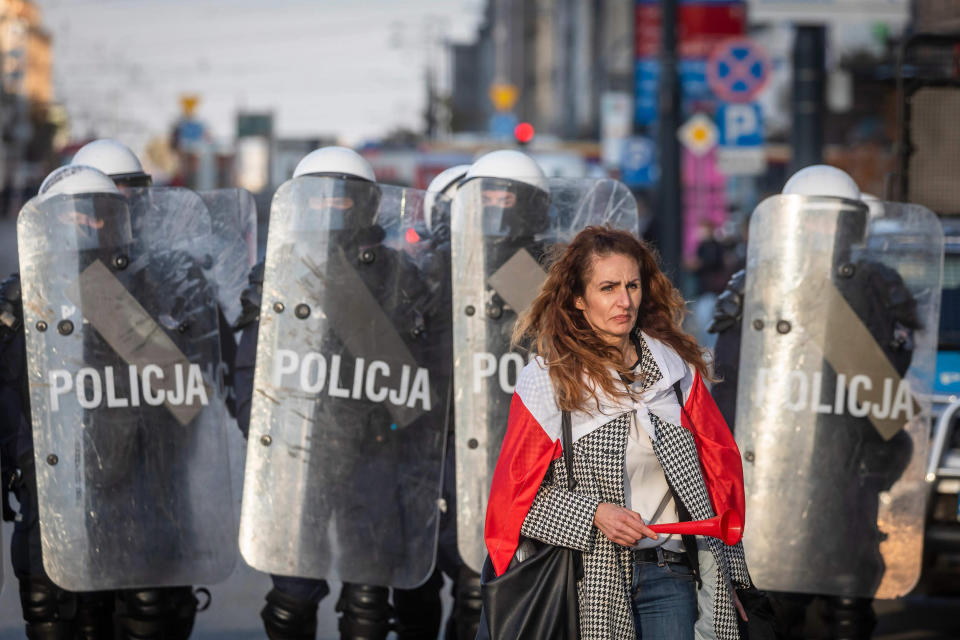 Image: A woman stands in front of Police during a demonstration against the coronavirus restrictions on Oct. 24, 2020 in Warsaw, amid the coronavirus Covid-19 pandemic. (Wojtek Radwanski / AFP - Getty Images)