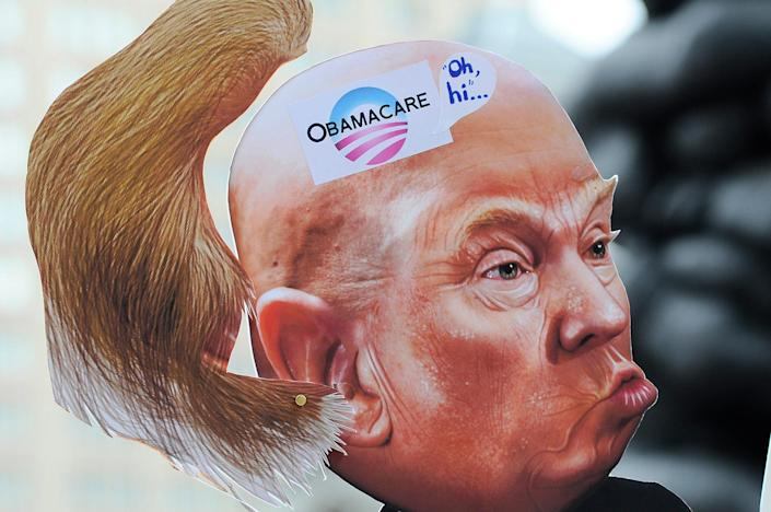 <p>Artist Carla Krash holds up a caricatutre of President Donald Trump at a protest against the repeal of the Affordable Care Act in Philadelphia, Feb. 25, 2017. (Photo: Bastiaan Slabbers/NurPhoto via Getty Images) </p>