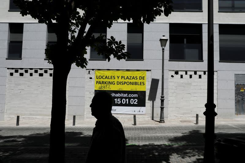 """FILE PHOTO: A man walks past a sign that reads """"Properties and parking available"""" on the wall of an apartment complex in Madrid"""