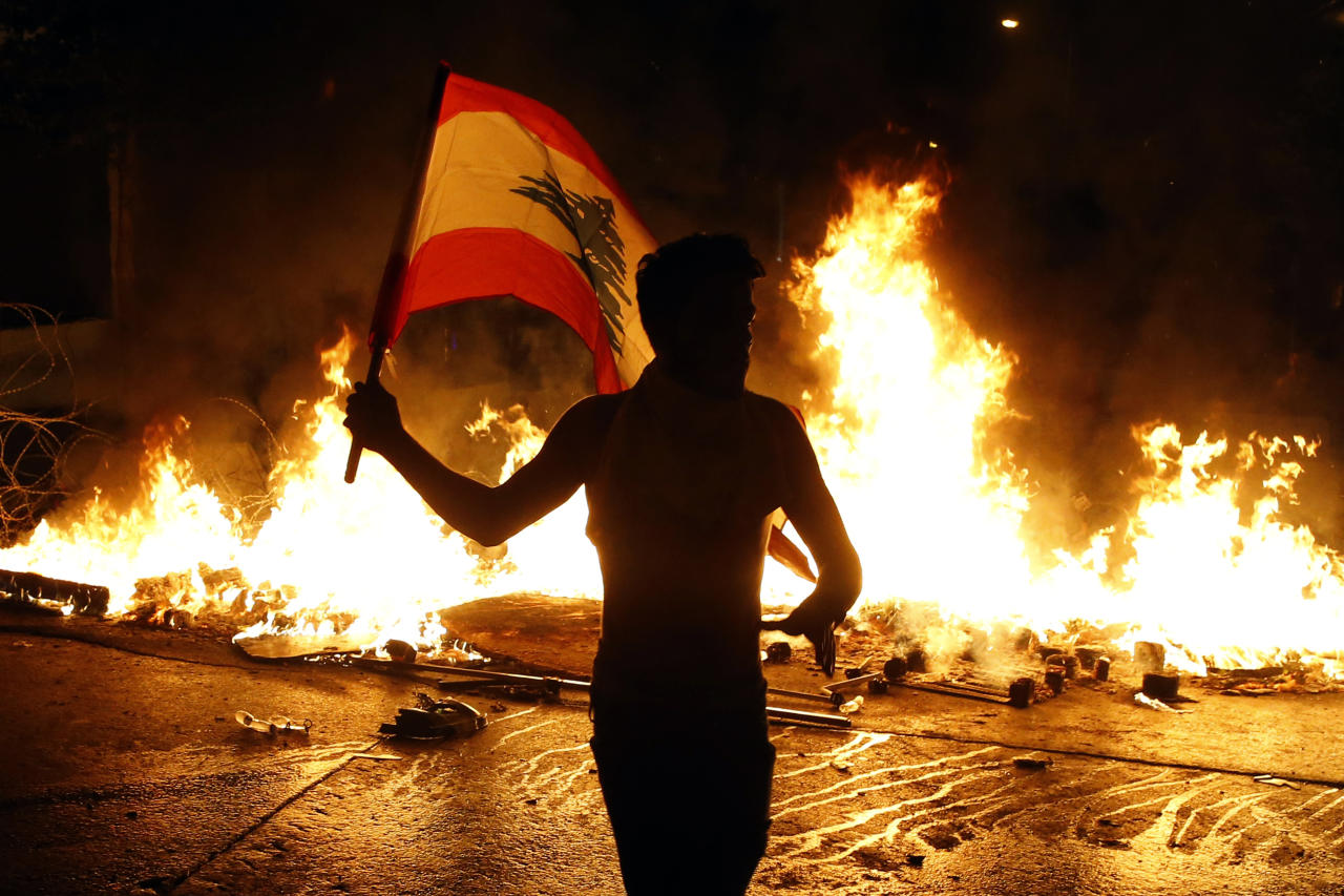 An anti-government protester waves a Lebanese flag in front of a barricade on fire on a road leading to the parliament building, during ongoing protests against the government, in Beirut, Lebanon, Wednesday, Nov. 13, 2019. Lebanese protesters said they will remain in the streets despite the president's appeal for them to go home. (AP Photo/Bilal Hussein)