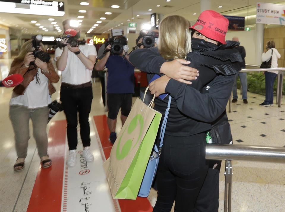 A woman arriving from New Zealand, right, is hugged by her stepmother at Sydney Airport in Sydney, Australia, Monday, April 19, 2021, as the much-anticipated travel bubble between Australia and New Zealand opens. (AP Photo/Rick Rycroft)