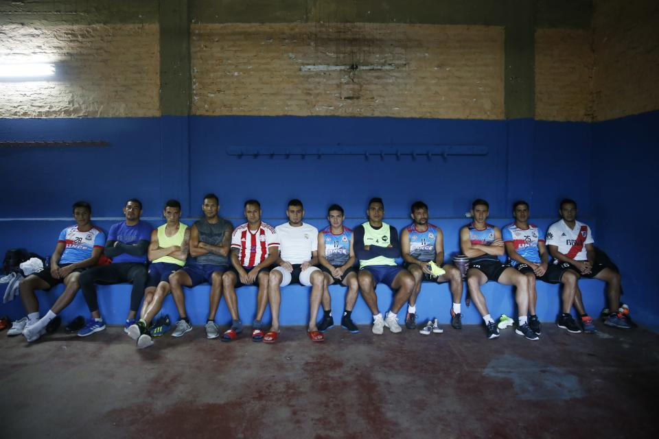 Striker Nicolas Caballero, fourth from right, of the second division Resistencia football club, takes a break with his teammates as they rest in the club's locker room in Asuncion, Paraguay, Tuesday, Feb. 2, 2021. Caballero, 32, who hasn't been paid by his club for more than a year, now has a food stall that sells barbecue on the streets to survive during the COVID-19 pandemic. (AP Photo/Jorge Saenz)