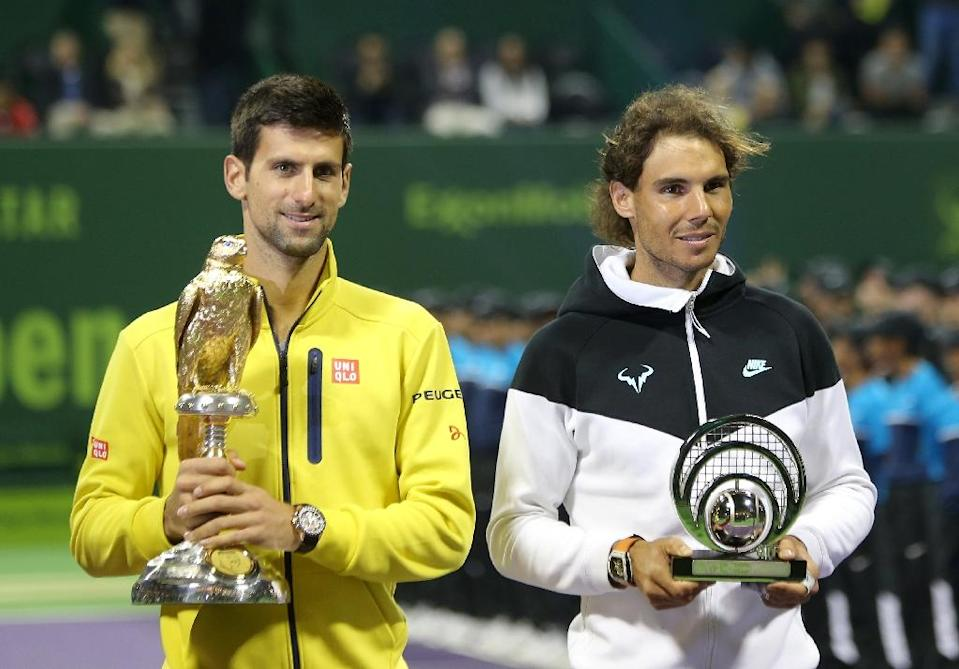 Novak Djokovic of Serbia (L) poses for a photo with his winning trophy next to Rafael Nadal of Spain holding his second place trophy following the final of the Qatar Open tennis tournament on January 9, 2016, in Doha (AFP Photo/Karim Jaafar)