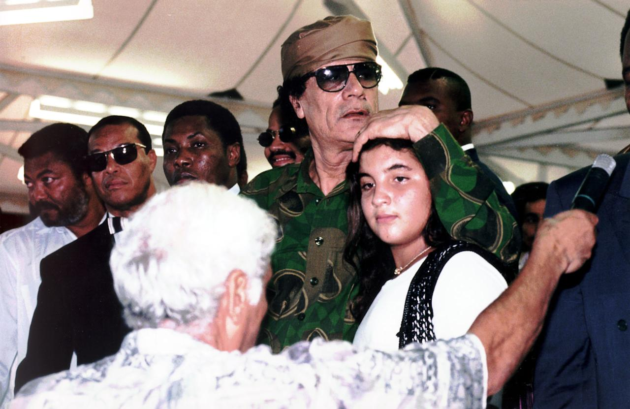 FILE - In this undated 1996 file photo, Col. Moammar Gadhafi holds his daughter Hana in Tripoli, Libya. Since the rebel takeover of Tripoli, evidence has been mounting that Moammar Gadhafi lied about the death of his adopted baby daughter Hana in a 1986 American airstrike. (AP Photo/Lino Azzopardi, File)