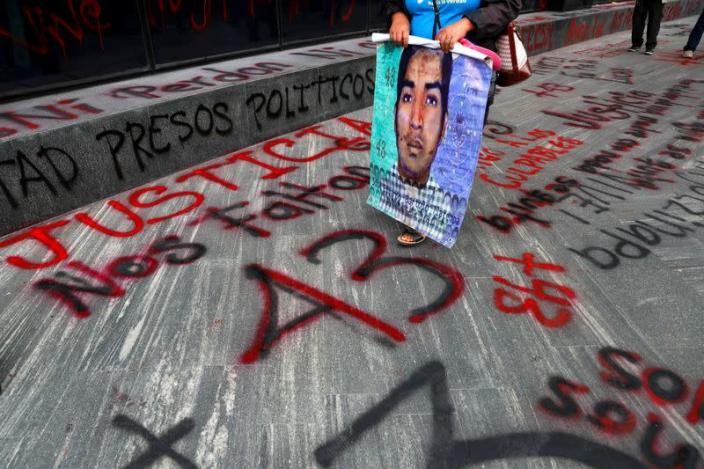 FILE PHOTO: A relative of a missing student holds a poster with his image during a protest outside the Attorney General's office, in Mexico City