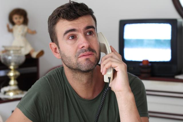 Man crying at home during phone conversation.