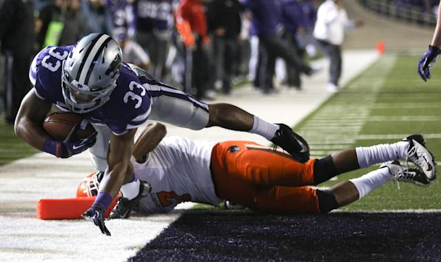 MANHATTAN, KS - NOVEMBER 03: Running back John Hubert #33 of the Kansas State Wildcats leaps into the end zone for a touchdown over Shamiel Gary #7 of the Oklahoma State Cowboys in first quarter at Bill Snyder Family Football Stadium on November 3, 2012 in Manhattan, Kansas. (Photo by Ed Zurga/Getty Images)