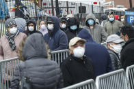 FILE - In this March 25, 2020, file photo, patients wear personal protective equipment while maintaining social distancing as they wait in line for a COVID-19 test at Elmhurst Hospital Center, in New York. As coronavirus rages out of control in other parts of the U.S., New York is offering an example after taming the nation's deadliest outbreak this spring — but also trying to prepare in case another surge comes. (AP Photo/John Minchillo)