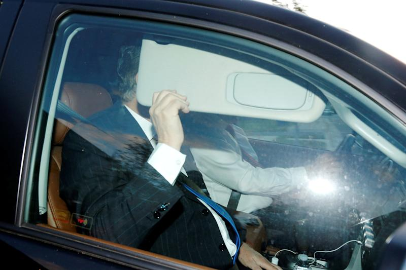 Paul Manafort hides behind his car visor as he leaves his home in Alexandria, Virginia, on Monday. (Jonathan Ernst / Reuters)