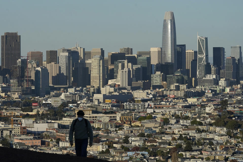 FILE - In this Dec. 7, 2020, file photo, a person wearing a protective mask walks in front of the skyline on Bernal Heights Hill during the coronavirus pandemic in San Francisco. California's population has declined for the first time in its history. State officials announced Friday, May 7, 2021, that the nation's most populous state lost 182,083 people in 2020. California's population is now just under 39.5 million. (AP Photo/Jeff Chiu, File)