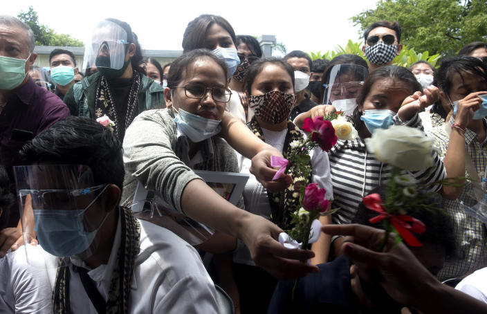 Relatives give flowers to pay their respect to Mia Tresetyani, a victim of the crash of Sriwijaya Air flight SJ-182 during her burial in Denpasar, Bali, Indonesia on Thursday, Jan. 21, 2021. The Indonesian leader on Wednesday reassured relatives of the passengers killed when the plane nosedived into the Java Sea that compensation is paid to family members struggled with grief. (AP Photo/Firdia Lisnawati)