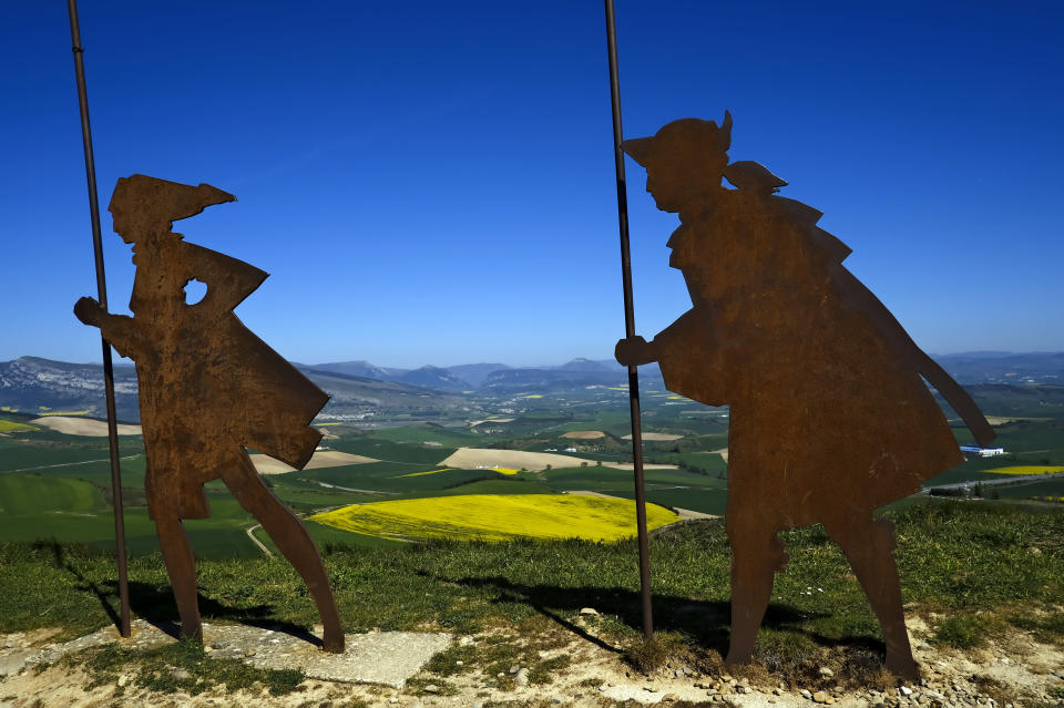 Sculptures representing St. James Way pilgrims are seen on top of a hill on the way to Santiago de Compostela around 15 kms, 9,3 miles, from Pamplona, northern Spain, Thursday, April 14, 2021. The pilgrims are trickling back to Spain's St. James Way after a year of being kept off the trail due to the pandemic. Many have committed to putting their lives on hold for days or weeks to walk to the medieval cathedral in Santiago de Compostela in hopes of healing wounds caused by the coronavirus. (AP Photo/Alvaro Barrientos)