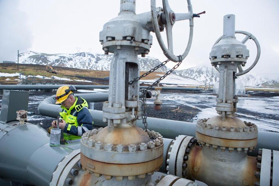A man works on a pipe beside a carbon injection site well near Reykjavik Energy's Hellisheidi Geothermal Power Plant, on December 4, 2017 outside Reykjavik, Iceland. To offset global warming, since year 2007, scientists have collaborated with Reykjavik Energy's experts, technicians, and tradespeople on developing the idea and implementation of fixating CO2 into basaltic rock.