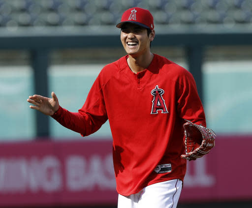 Los Angeles Angels' Shohei Ohtani laughs with his interpreter as players warm up for a baseball game against the Kansas City Royals in Anaheim, Calif., Tuesday, June 5, 2018. (AP Photo/Alex Gallardo)