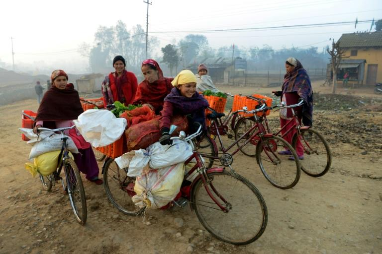 Female vendors, using their bicycles to carry their vegetables, arrive to sell their wares at a market in Nepal this February