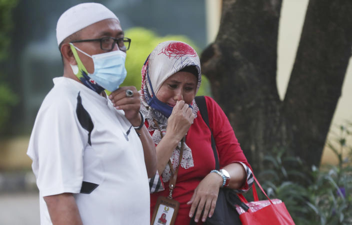 Relatives of Panca Widia Nursanti, a victim in the Sriwijaya Air passenger jet crash, cry at a hospital in Jakarta, Indonesia, Tuesday, Jan. 12, 2021. Indonesian navy divers were searching through plane debris and seabed mud Tuesday looking for the black boxes of the Sriwijaya Air jet that nosedived into the Java Sea over the weekend with 62 people aboard. (AP Photo/Achmad Ibrahim)