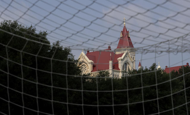St. Edwards University main building is seen through a soccer goal, Tuesday, May 5, 2020, in Austin, Texas. In response to the economic impact of COVID-19, the St. Edwards says they are cutting cut six sports programs including men's and women's tennis, men's and women's golf and men's soccer. (AP Photo/Eric Gay)