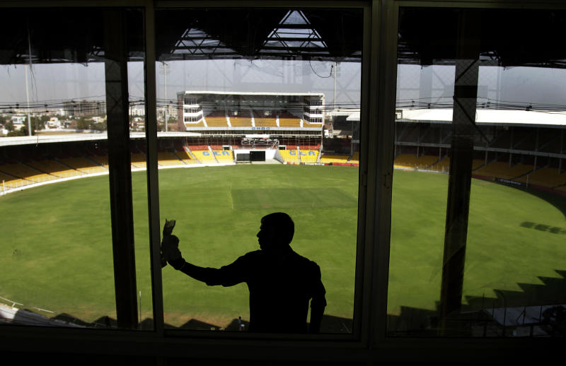 An Indian man cleans a glass at the Sardar Patel Stadium, one of the venues for the upcoming ICC Cricket World Cup in Ahmadabad, India, Wednesday, Feb. 9, 2011. The ICC World Cup Cricket is slated to begin Feb. 19. (AP Photo/Ajit Solanki)