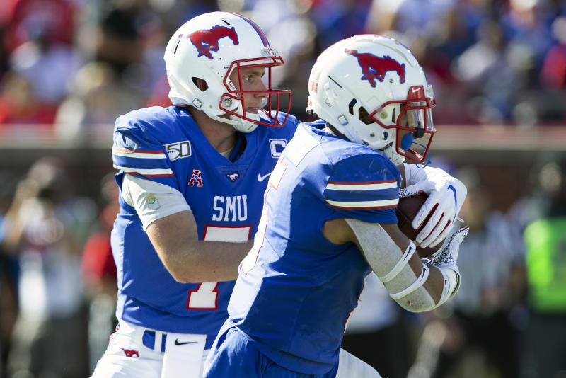 SMU quarterback Shane Buechele (7) hands the ball off to running back Xavier Jones (5) during the second quarter of an NCAA college football game against Temple in Dallas, Saturday, Oct. 19, 2019. (AP Photo/Sam Hodde)