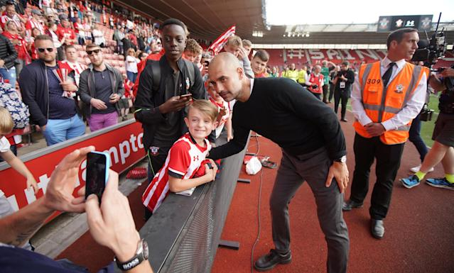 "Soccer Football - Premier League - Southampton vs Manchester City - St Mary's Stadium, Southampton, Britain - May 13, 2018 Manchester City manager Pep Guardiola poses for a photograph with a Southampton fan after the match REUTERS/David Klein EDITORIAL USE ONLY. No use with unauthorized audio, video, data, fixture lists, club/league logos or ""live"" services. Online in-match use limited to 75 images, no video emulation. No use in betting, games or single club/league/player publications. Please contact your account representative for further details."