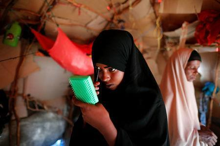Zeinab, 14, applies her makeup before heading to school inside her shelter at a camp for internally displaced people from drought-hit areas in Dollow, Somalia April 4, 2017. REUTERS/Zohra Bensemra