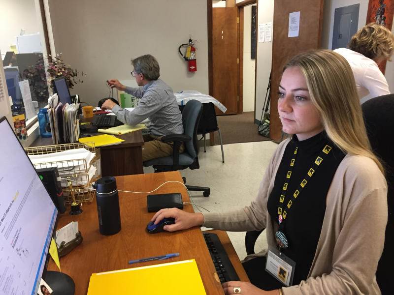 Megan Schwab, a community engagement specialist with the International Rescue Committee of Boise, works at her desk, Tuesday, July 3, 2018, in Boise, Idaho. Schwab is friends with Ethiopian refugee Bifituu Kadir and her daughter, Ruya Kadir. Three-year-old Ruya died Monday from wounds she received when a man armed with a knife attacked her birthday party, injuring nine people. (AP Photo/Rebecca Boone)