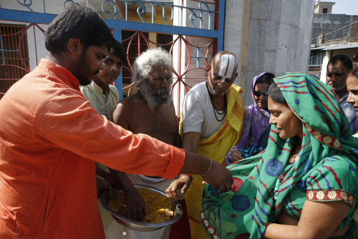 Hindus distribute sweets to celebrate the verdict in a decades-old land title dispute between Muslims and Hindus, in Ayodhya, India , Saturday, Nov. 9, 2019. India's Supreme Court on Saturday ruled in favor of a Hindu temple on a disputed religious ground and ordered that alternative land be given to Muslims to build a mosque. The dispute over land ownership has been one of the country's most contentious issues. (AP Photo/Rajesh Kumar Singh)
