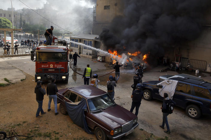 Firefighters extinguish a police car that was set on fire by anti-government protesters, in the northern city of Tripoli, Lebanon, Tuesday, April 28, 2020. Hundreds of angry Lebanese took part Tuesday in the funeral of a young man killed in riots overnight in Tripoli that were triggered by the crash of Lebanon's national currency that sent food prices soaring. (AP Photo/Bilal Hussein)
