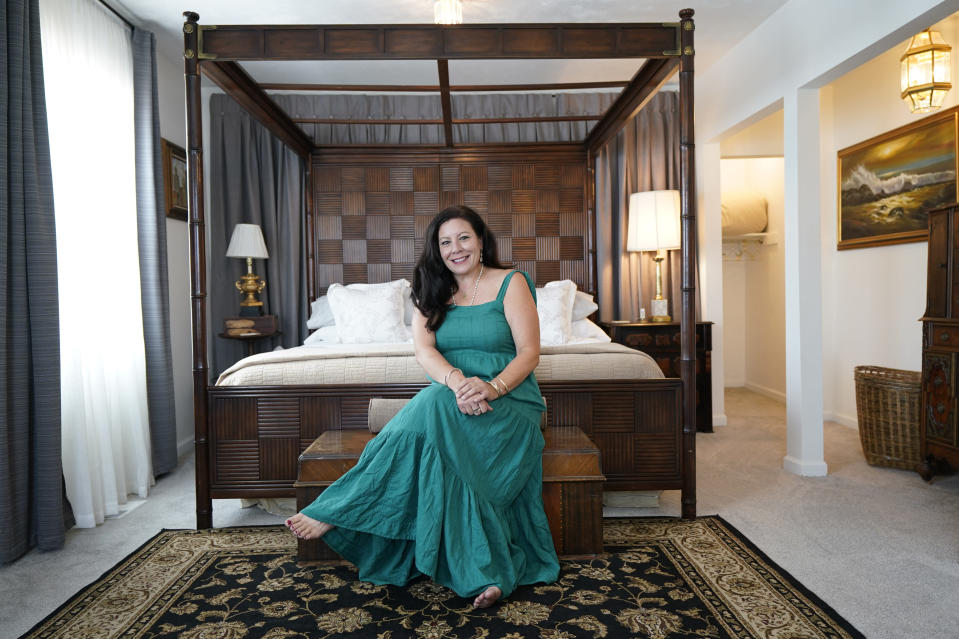 """Heather Bise, owner of The House of Bise Bespoke, poses in the """"Art"""" bedroom, Monday, July 19, 2021, in Cleveland. Small businesses in the U.S. that depend on tourism and vacationers say business is bouncing back, as people re-book postponed trips and take advantage of loosening restrictions, a positive sign for the businesses that have struggled for more than a year. Bise started in 2019 and catered to international tourists, attracting guests from New Zealand, Botswana, Eastern Europe and elsewhere. (AP Photo/Tony Dejak)"""