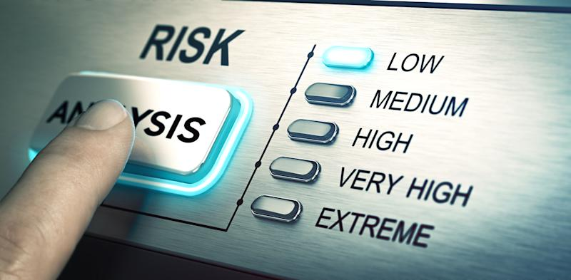A person pushing a risk analysis button that is highlighting the word low