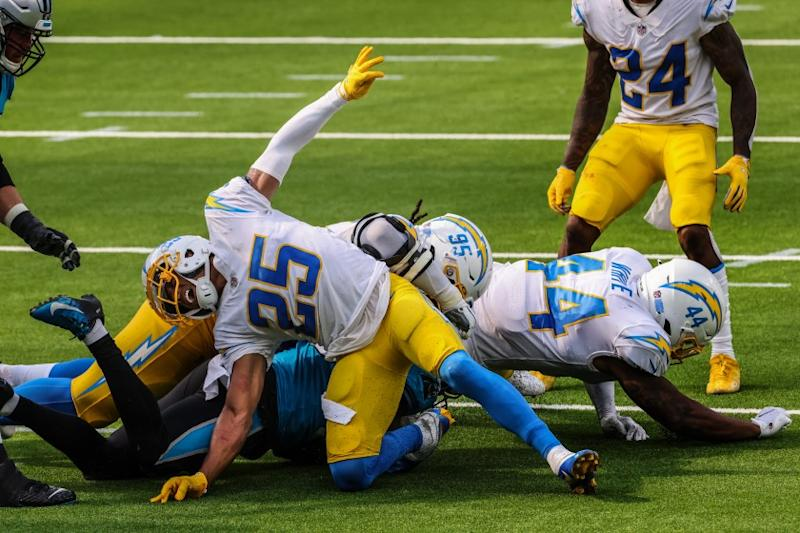 Inglewood, CA, Sunday, September 27, 2020 - Los Angeles Chargers cornerback Chris Harris (25) writhes in pain after injuring his leg while stuffing runner Carolina Panthers running back Mike Davis (28) at SoFi Stadium. (Robert Gauthier/ Los Angeles Times)