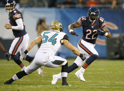 Chicago Bears running back Matt Forte (22) tries to avoid a tackle by Jacksonville Jaguars linebacker Nate Stupar (54) during the first half of an NFL preseason football game in Chicago, Thursday, Aug. 14, 2014. (AP Photo/Andrew Nelles)