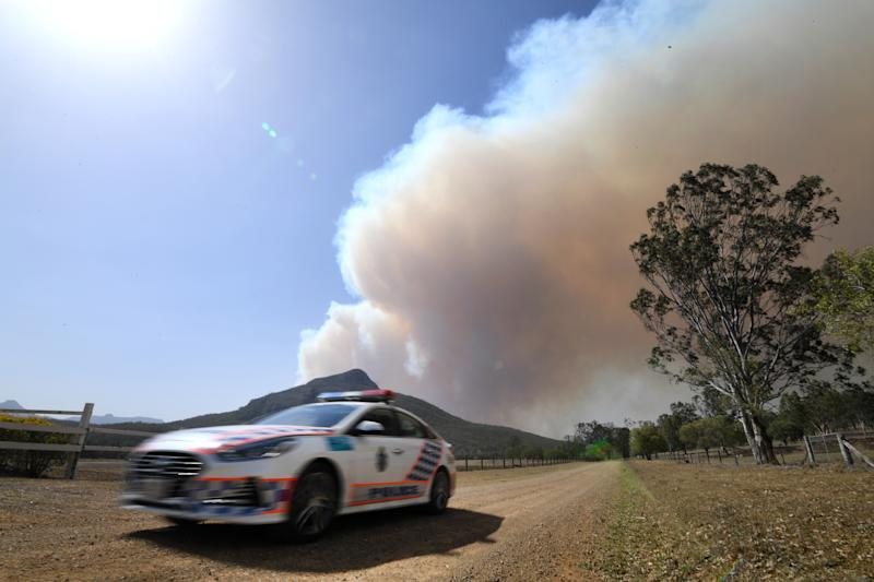 A police vehicle is seen as smoke from an out-of-control bushfire billows in the distance near Clumber, Queensland, Friday, November 8, 2019. Extreme fire warnings are in place for parts of south east Queensland with high temperatures and strong winds. (AAP Image/Dan Peled) NO ARCHIVING