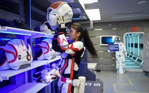 """A guide wearing a spacesuit puts on a helmet at """"Mars Base 1"""", a C-Space Project - Credit: Wang Zhao AFP"""