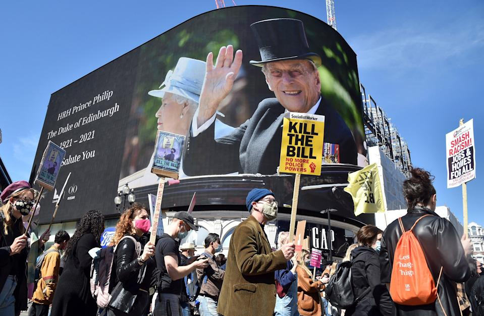<p>Protesters walk past images of Britain's Prince Philip displayed on a giant screen at Piccadilly Circus</p> (AP)