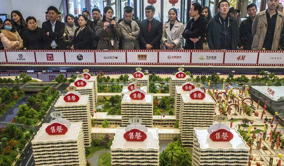 Prospective customers look at a model of the Dalian Wanda Group's property project in Qingdao, China. Photo: Bloomberg